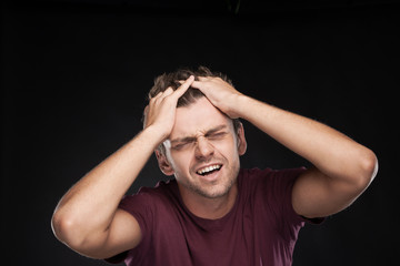 Portrait of Man Holding His Head in Stress.