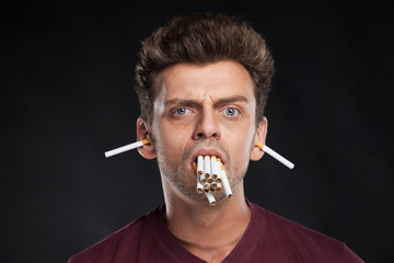 Man holding many cigarettes in his mouth.