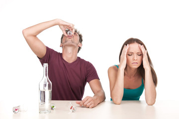 Man drinking alcohol and woman sitting upset at table.