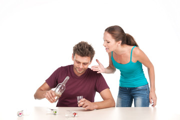 Man drinking alcohol and woman shouting at him.