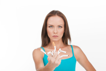 young woman breaking up cigarette isolated on white background.