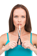 brunette woman cutting cigarette with scissors.