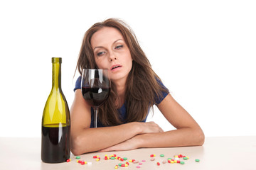 Pills lying on table with bottle of wine on white background