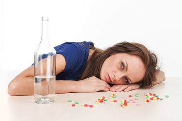 Pills scattered on table with bottle on white background.