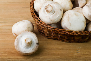 Basket with mushrooms on a wooden background