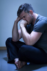 Depressed man sitting on the floor