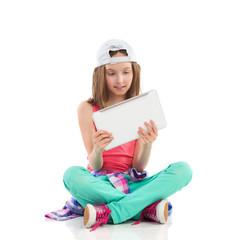 Little girl reading something on a digital tablet.