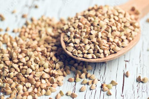 uncooked buckwheat on wooden spoon - 68764491