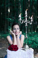 smiling girl sits at a table with a bouquet of red roses and sil