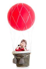 child on hot air balloon watching through spyglass