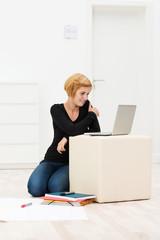 junge frau mit laptop in einem leeren büro