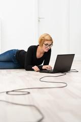 junge frau in einem leeren zimmer mit laptop