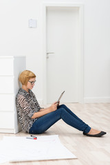 frau liest am tablet in einem leeren büro