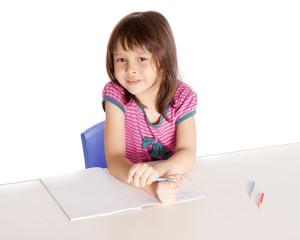 Girl doing homework smiling at camera