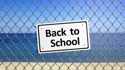 Beach enclosed by fence with sign Back to School