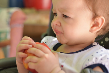 Cute little girl eating peach
