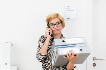 genervte frau mit akten und telefon im büro