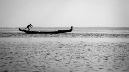 Gondolier in the Venice lagoon backlight