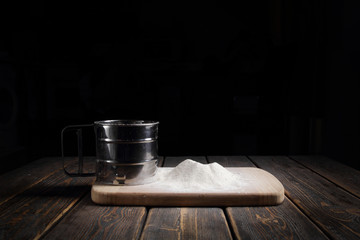 Sieve flour on wooden table