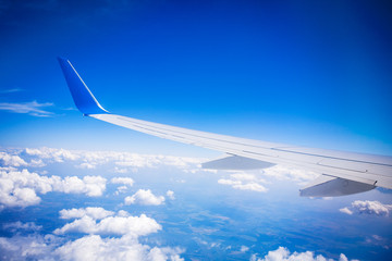 airplane wing with blue sky and white clouds