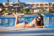 attractive young women posing on the poolside