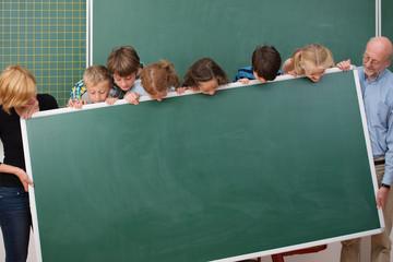 schulkinder und lehrer schauen auf eine tafel