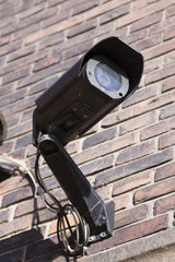 CCTV camera mounted on red brick wall.