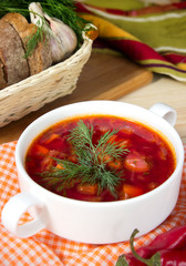Borsch in white bowl .Red beetroot traditional soup closeup.