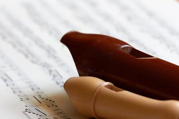 Blockflöte und Altflöte auf Notenpapier