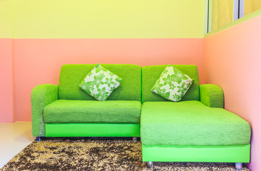 Green sofa in pink room