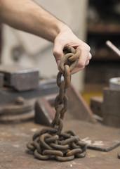 Man making streght against a chain