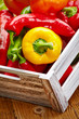 Colorful peppers in a wooden box