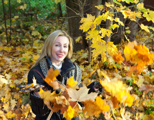 beautiful woman in autumn park throws up maple leaves