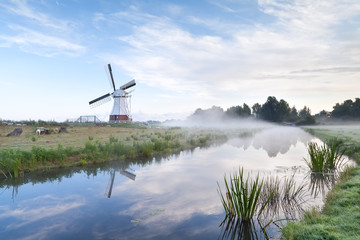 Dutch windmill by river in morning