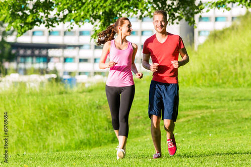 canvas print picture Freunde joggen gemeinsam durch den Park