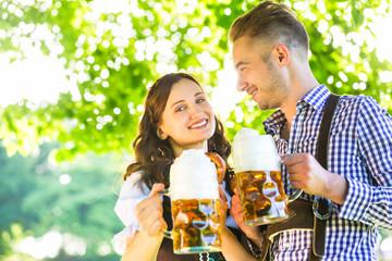 Deutsches Paar in Tracht trinkt Bier