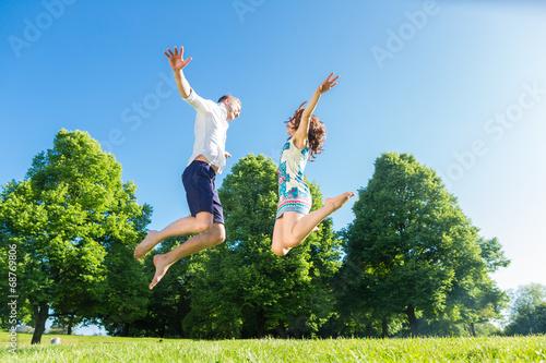 canvas print picture Paar springt verliebt auf Park Wiese