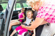 Mutter schnallt Kind im Auto Kindersitz an