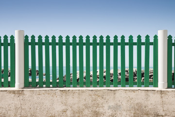 Green fence in front of the sea
