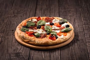 Pizza with salami, mozzarella, olives and basil on wooden table