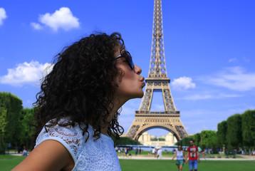Beautiful girl kisses Eiffel tower, Paris, France