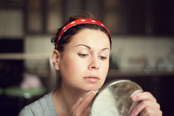 young woman taking care of her face at home