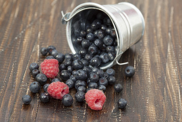 Blueberries and raspberries in a small bucket scattered on a woo