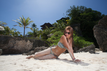 Young beautiful woman lying on the sand