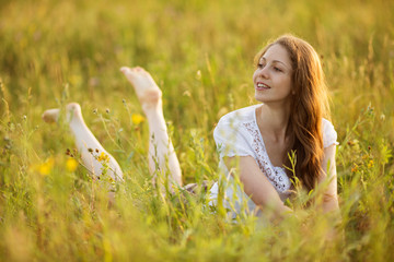 Young happy woman looks out of grass