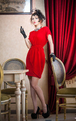 Beautiful woman in red with gloves and creative hairstyle posing
