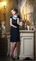 Young beautiful brunette woman in elegant black dress standing