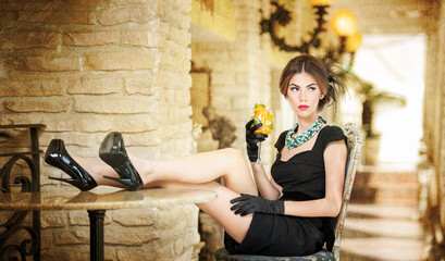 Fashionable attractive young woman in black dress relaxing