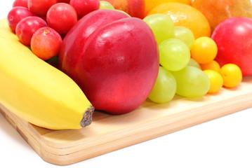 Fresh ripe fruits on wooden cutting board
