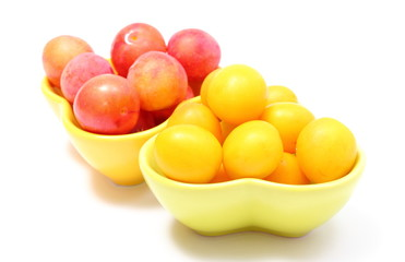 Heap of red and yellow mirabelle in bowls. White background